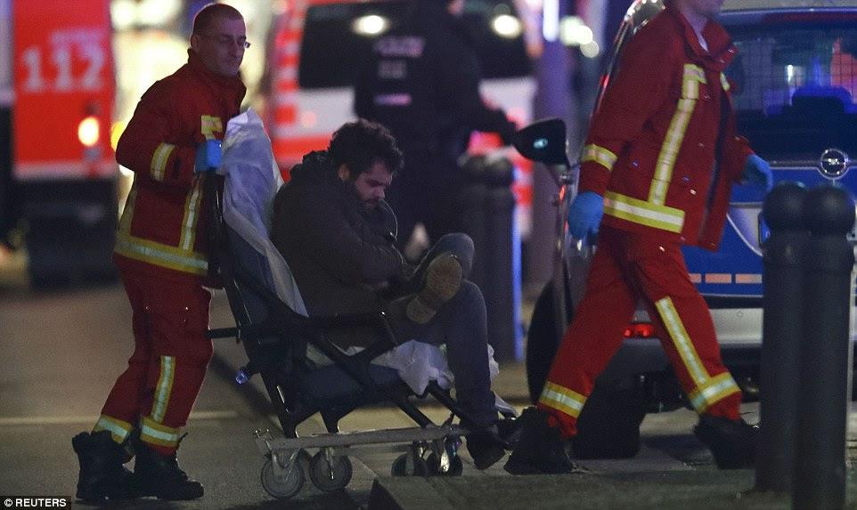 Um homem ferido é empurrado para uma ambulância no local de um acidente como dezenas de outros são tratados na cena do crime