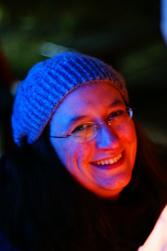 Me smiling, wearing a grey knitted hat. My face is yellow and red on the side lit by the lantern, and blue on the shadow side