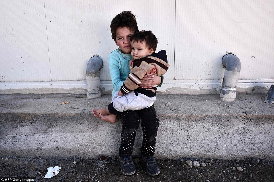 A girl and her brother wait at the reception centre for migrants and refugees in Schisto, near Athens, where 1,300 migrants, mainly Afghans, are stranded