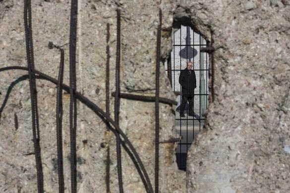A man is seen through a hole in the former Berlin Wall at the corner of Wilhelmstrasse and Niederkirchner in Berlin March 4, 2013. REUTERS-Thomas Peter