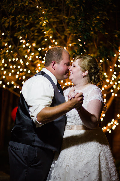 Romantic Photos taken outside at night at Blumen Gardens in Sycamore IL with the bride and groom under a vine covered trellis with Christmas Lights.