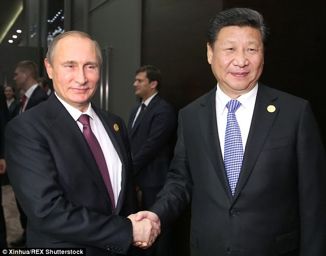 Mr Putin was pictured smiling and posing for photos with Chinese President Xi Jinping during the G20 summit in Turkey