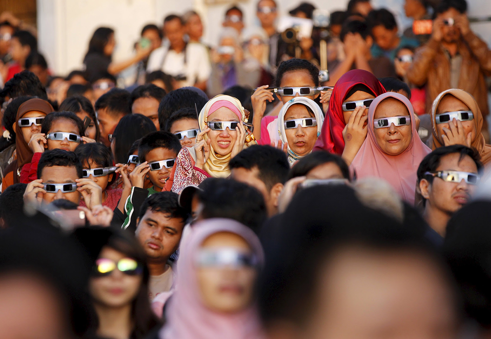 People watch a solar eclipse outside the planetarium in Jakarta, Indonesia