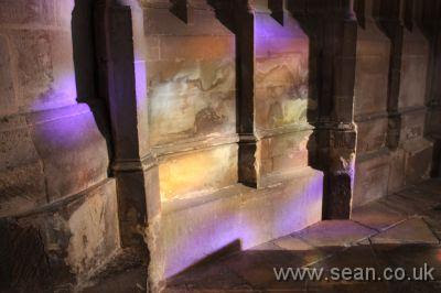 purple, yellow and green light shining through a stained glass window onto the stonework of Gloucester Cathedral