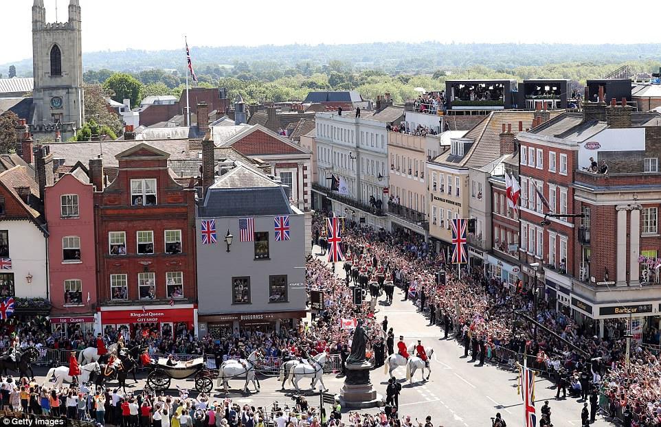 Fãs reais pareciam se inclinar para fora das janelas e ficar de pé sobre os telhados enquanto a procissão percorria a rua principal de Windsor.