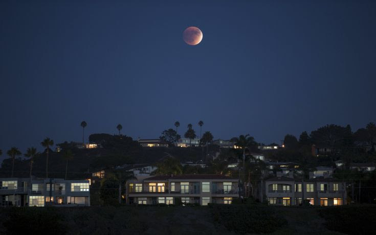 A blood moon rises behind hilltop residences in Solana Beach