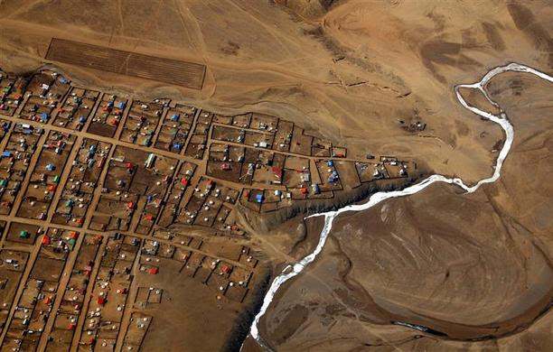 A frozen river is seen next to a group of houses located on the outskirts of the Mongolian capital city of Ulaanbaatar, April 3, 2012. REUTERS-David Gray )