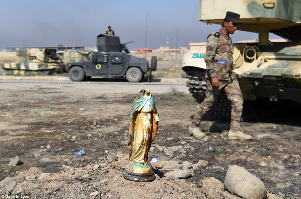An Iraqi soldier walks past of broken statue of the Virgin Mary after liberating the town of Bartella, which has a Christian population