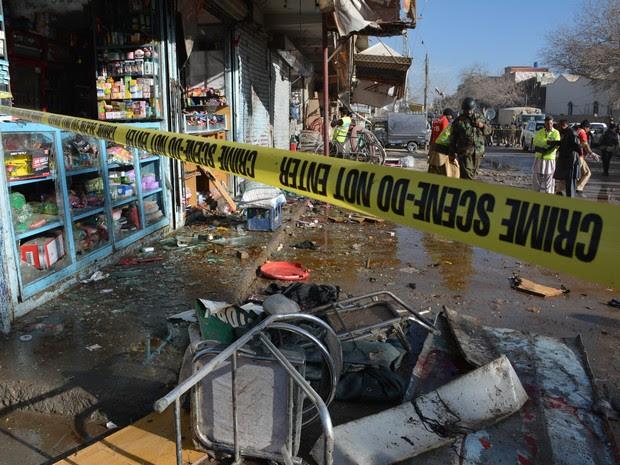 Policiais examinam local de explosão de bomba próximo a centro de vacinação contra poliomielite no Paquistão (Foto: Banaras Khan/AFP)