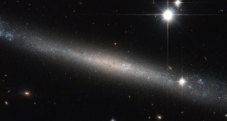 a thin sliver of a galaxy seen edge on - one of the flattest Hubble has imaged - with two bright stars burning upper right
