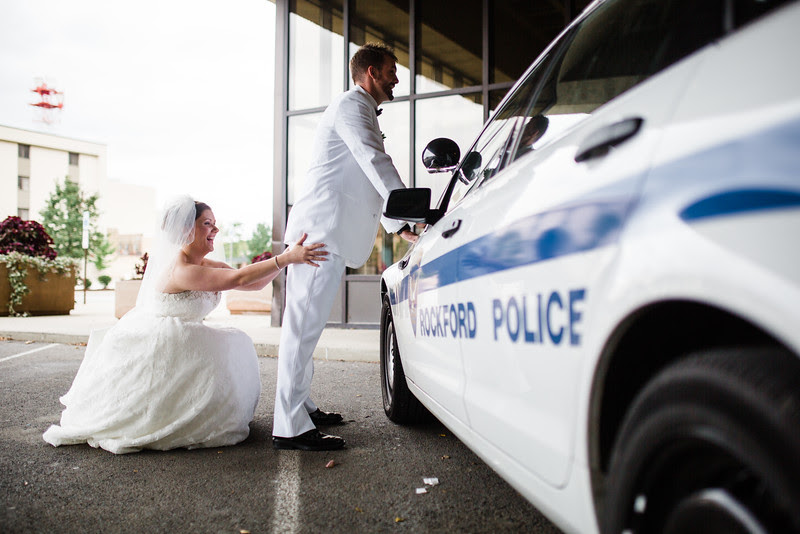 The Bride frisks the Groom on a police squad car following their wedding at Court Street United Methodist Church in downtown Rockford Illinois for an Autumn wedding.