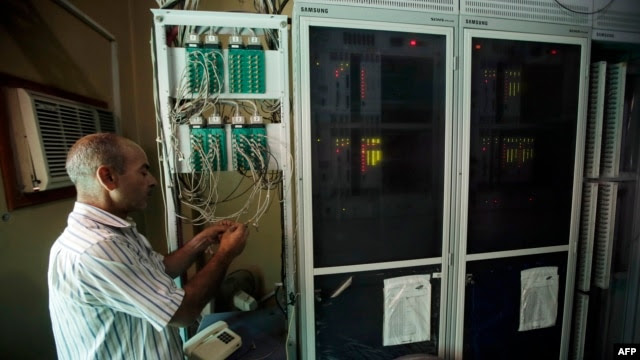A Syrian techinician works to set a new telephone network in the city of Qusayr, in Syria's central Homs province, Aug. 1, 2013.
