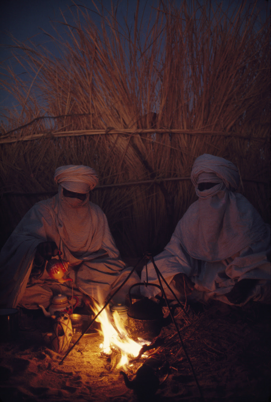 Tuareg goatherds drink tea in their desert shelter at Hassi Izernene, August 1973.Photograph by Thomas J. Abercrombie, National Geographic