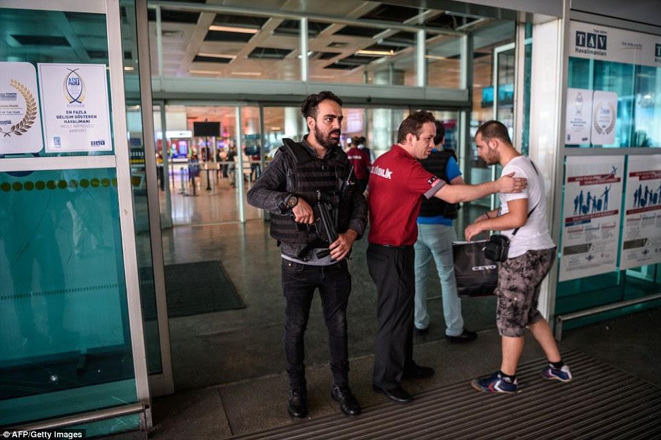 Um agente da polícia turca anti motim e um empregado de uma empresa de segurança privada verificar um passageiros que entram no terminal de chegada do aeroporto internacional Ataturk esta manhã