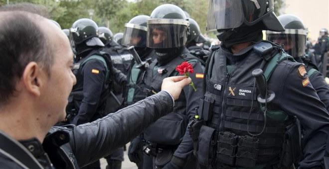 Un hombre ofrece un clavel a un agente de la Guardia Civil en el centro de votación de Sant Julià de Ramis (Girona) donde inicialmente tenía previsto votar el presidente de la Generalitat, Carles Puigdemont, en el referéndum independentista del 1-O./ EFE