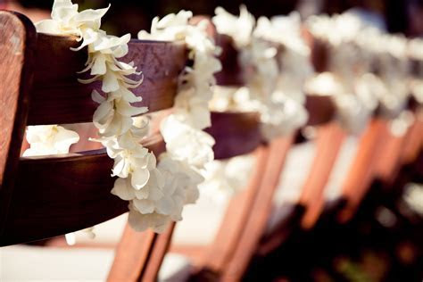 Single strand white orchid leis draped over ceremony
