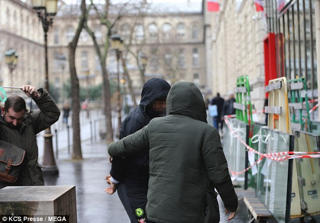 A handcuffed man was seen being led in to a police station in Paris following the raids yesterday