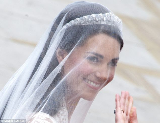 The first glimpse: An assured smile from behind her veil and a wave as she arrives at the Abbey