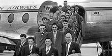 Một bức ảnh đen trắng của một số người trong bộ quần áo và áo khoác trên cầu thang của một chiếc máy bay.