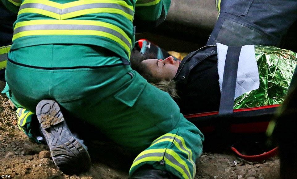 Μετέφερε με ασφάλεια: Ένας εθελοντής παίζει μια γυναίκα τραυματίστηκε στην κατάρρευση είναι δεμένο σε ένα φορείο πριν μεταφερθούν έξω από το σταθμό