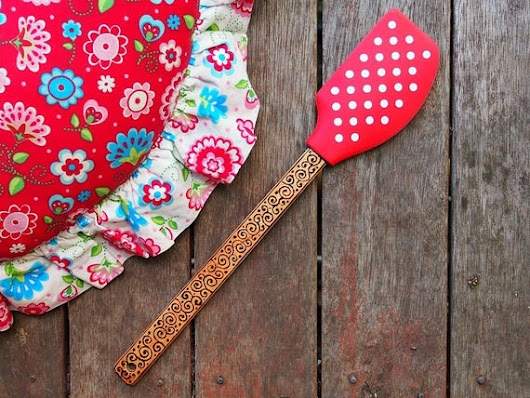 Red polka dot wood-burned rubber spatula with scrolls and