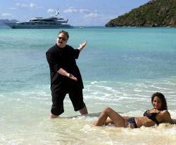 Kim Dotcom con modelo en la playa