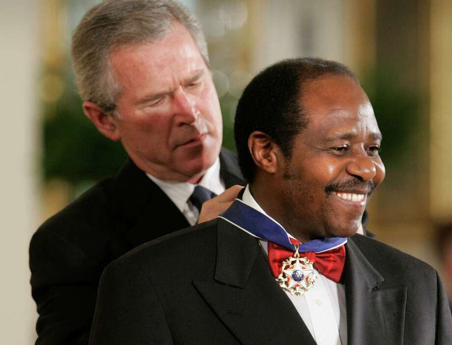 President Bush awards, Paul Rusesabagina, who sheltered people at a hotel he managed during the 1994 Rwandan genocide, the Presidential Medal of Freedom Award in the East Room of the White House, Wednesday, Nov. 9, 2005, in Washington. The Presidential Medal of Freedom is the highest civilian award given.(AP Photo/Lawrence Jackson) Photo: LAWRENCE JACKSON, STF / AP / AP