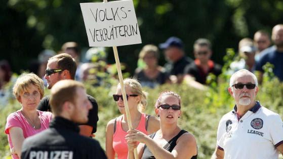 """Menschen in Heidenau halten am 26. August ein Schild in die Höhe: Mit dem Wort """"Volksverräterin"""" greifen sie Kanzlerin Angela Merkel (61, CDU) an"""