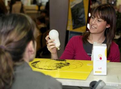 Una joven obtiene una bombilla de bajo consumo en una oficina de Correos de Zaragoza