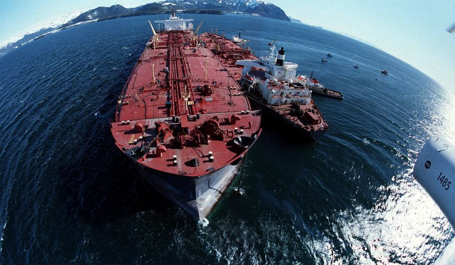 In this April 4, 1989, file photo, the grounded tanker Exxon Valdez, left, unloads oil onto a smaller tanker, San Francisco, as efforts to re-float the ship continue on Prince William Sound, 25 miles from Valdez, Alaska. The 987-foot tanker, carrying 53 million gallons of crude, struck Bligh Reef at 12:04 a.m. on March 24, 1989, and within hours unleashed an estimated 10.8 million gallons of thick, toxic crude oil into the water. Storms and currents then smeared it over 1,300 miles of shoreline. Twenty five years later, the region, its people and its wildfire are still recovering. (AP Photo, File) **FILE**