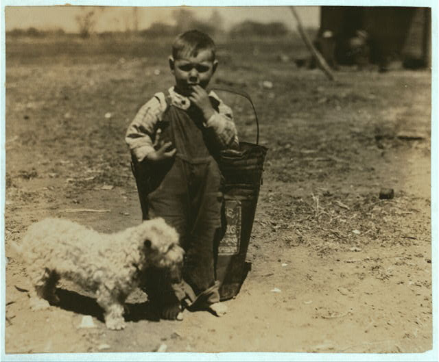 [Small boy standing outdoors with dog].  Location: Oklahoma City, Oklahoma.
