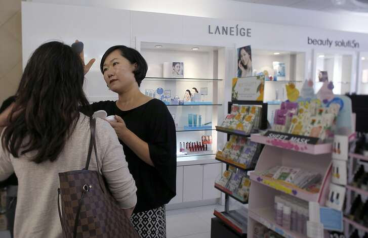 Amore sales associate Sarah Jung applies make up to a customer in Santa Clara, Calif., on Thursday, August 20, 2015.