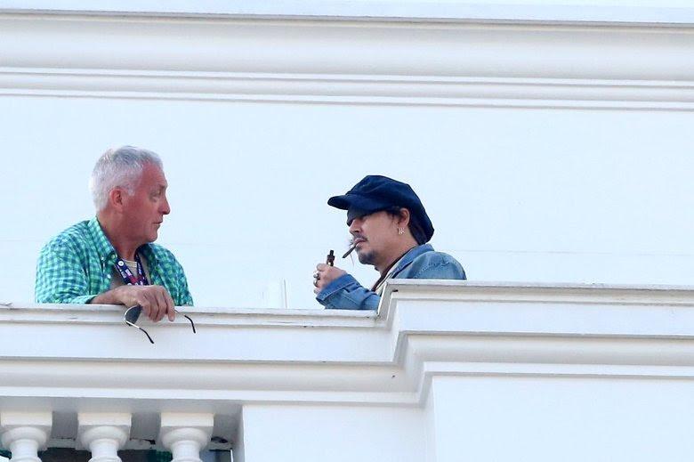 Johnny Depp aparece fumando em sacada de hotel