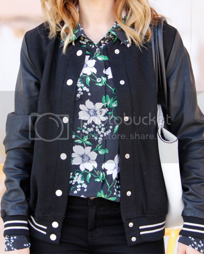Fashion blogger The Key To Chic wears an Equipment floral silk blouse, Forever 21 varsity jacket with faux leather sleeves, and J Brand skinny jeans in black