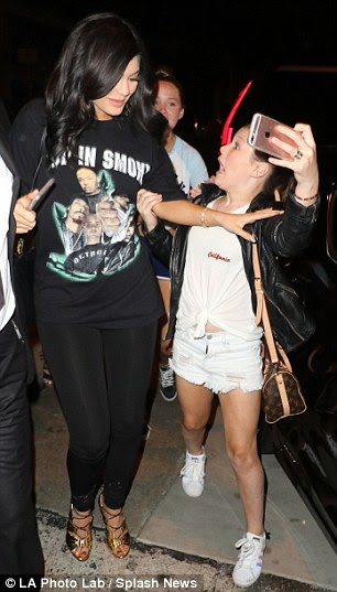 Get a grip: The girl grabbed Kylie's arm as she pushed for the photo