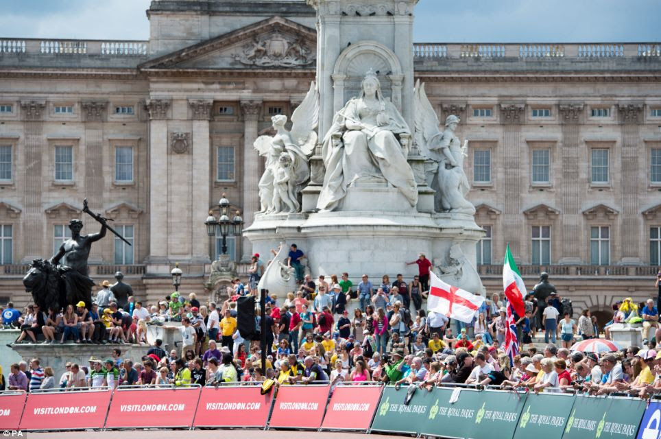 Showing support: Fans lined the streets today - including outside Buckingham Palace - as they cheered on the riders on stage three of the Tour