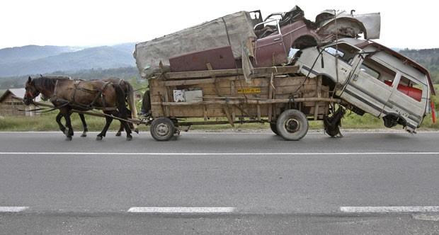 Em setembro de 2010, uma carroça foi fotografa supercarregada em Costesti, na Romênia. A carroça levava, inclusive, a carcaça de uma van. (Foto: Vadim Ghirda/AP)