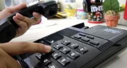 Mulher discando telefone fixo