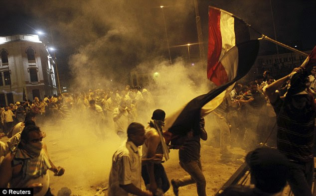 Battle: Supporters of deposed Egyptian President Mohamed Morsi run from tear gas fired by riot police during clashes at Ramses Square in Cairo last night