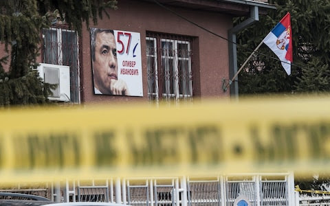 A poster bearing a picture of Oliver Ivanovic hangs on the wall of his offices after he was killed in a brazen drive-by shooting in Mitrovica