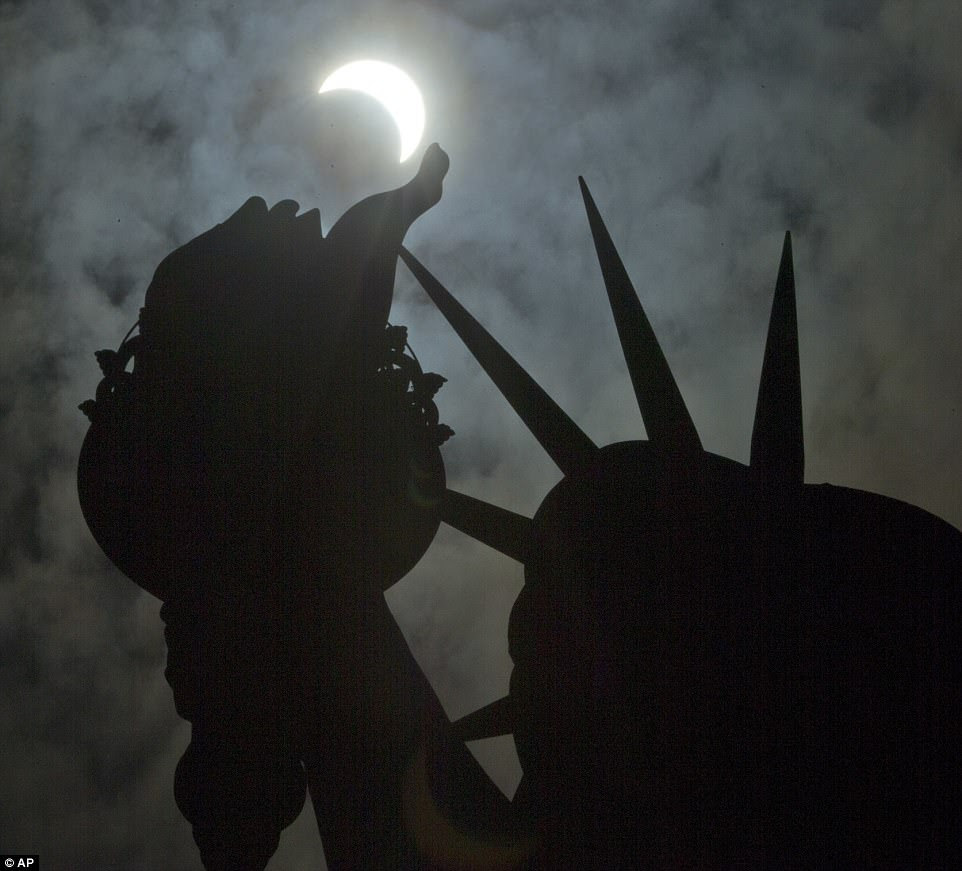 A partial solar eclipse is seen near the Statue of Liberty on Liberty Island in New York, Monday