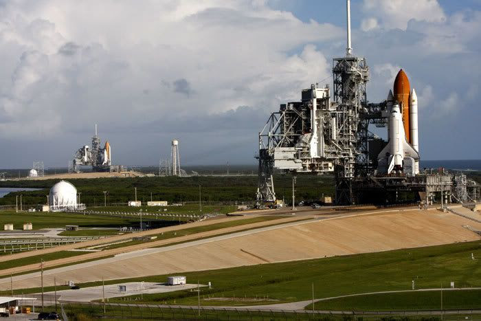 Space shuttle Atlantis stands ready for launch at Kennedy Space Center's Pad 39A in the foreground, while in the background, at Pad 39B 1.6 miles away, Endeavour begins preps for a potential rescue mission to Atlantis if she is found damaged during next month's flight to the Hubble Space Telescope.