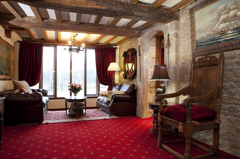 The large reception area is furnished with large leather chairs a stag light stand and a antique wooden chair