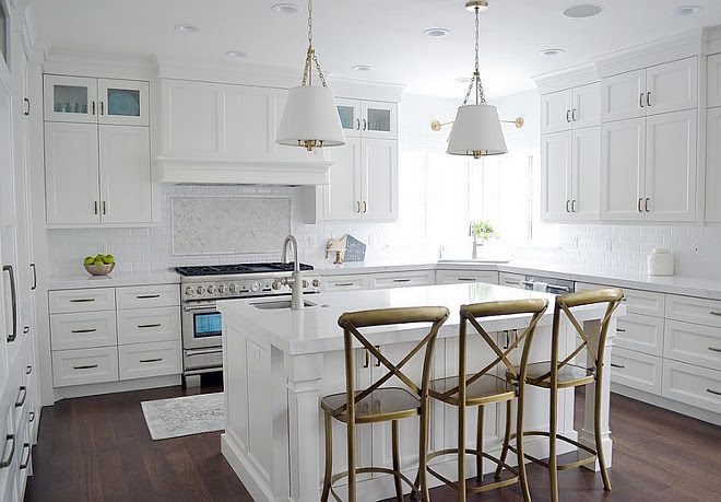 All white kitchen ideas. This kitchen features gorgeous quartz countertops, a white beveled subway tile, with a pretty marble herringbone accent, beautiful brass hardware and lighting. #Whitekitchen #allwhitekitchen Sita Montgomery Interiors
