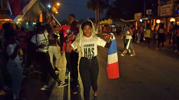 People celebrate in the streets after hearing of the confirmed departure of former Gambian leader Yahya Jammeh in Banjul on January 21, 2017