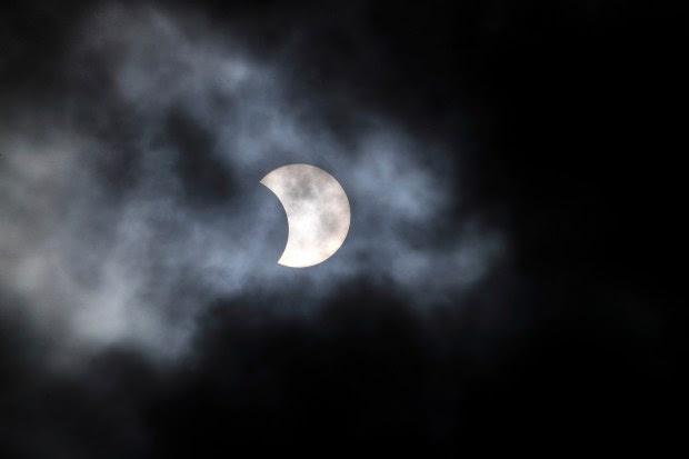 A phase of a partial solar eclipse is shown through cloud cover in Detroit, Monday, Aug. 21, 2017. (AP Photo/Paul Sancya)