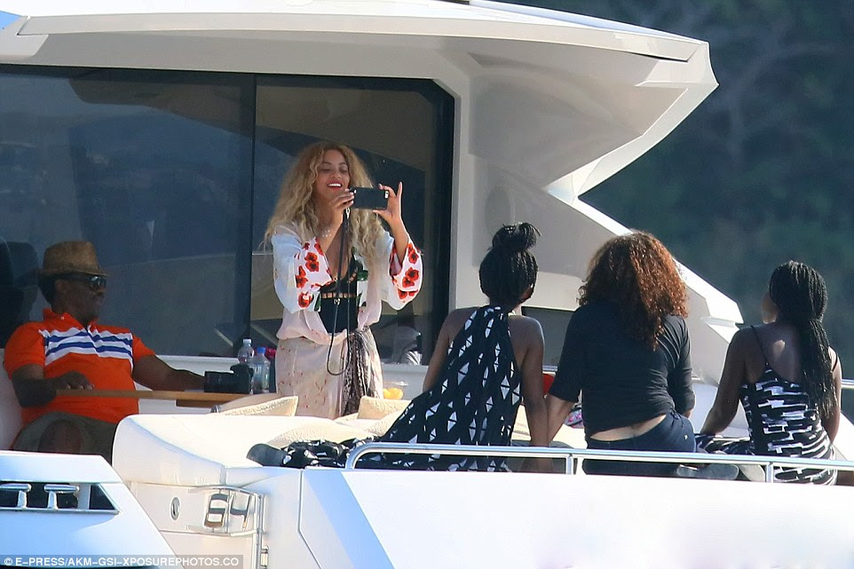 Say cheese: Beyonce looked to be making memories, and snapped a picture of three of her friends at one point