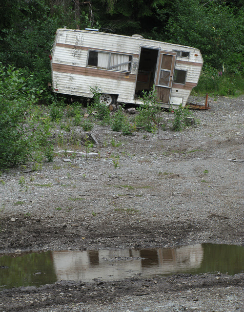 abandoned trailer reflects in a puddle, Kasaan, Alaska