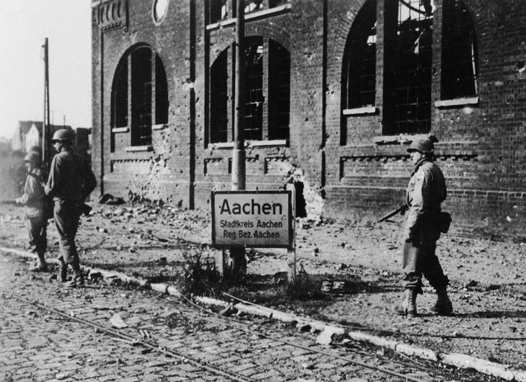 Soldiers of the 504th Parachute Infantry Regiment move through Aachen, Germany, April 1945
