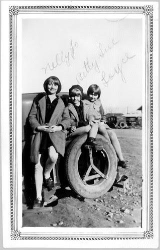 Three kids on rear of car